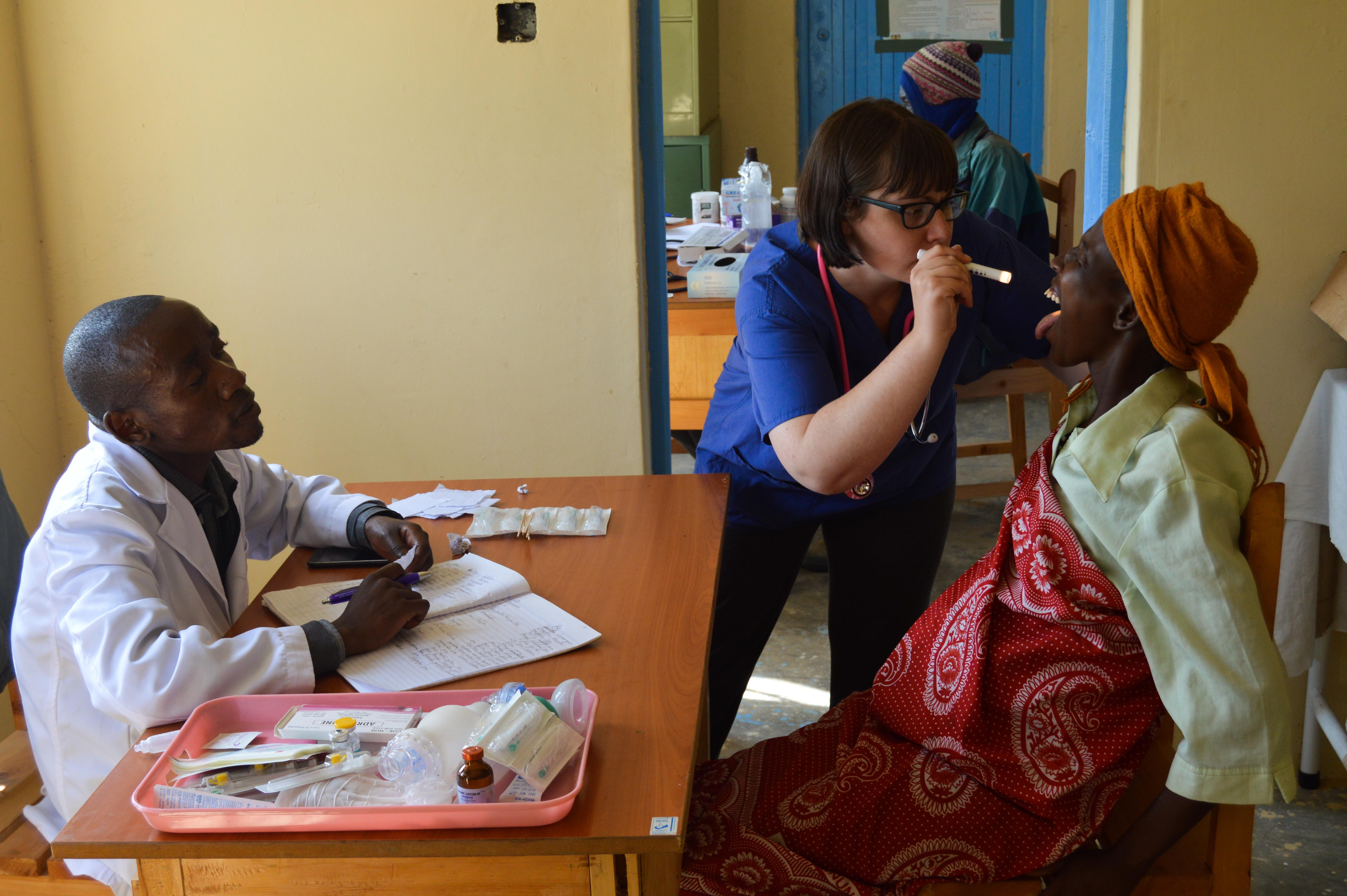 Female medical intern examines a woman's mouth with a healthcare worker at a medical outreach in Kenya.